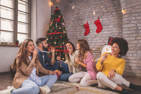 Group of young friends sitting by nicely decorated Christmas tree, celebrating Christmas at home, having fun while exchanging and opening presents