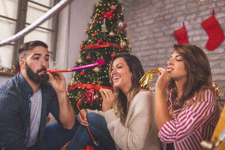 Group of young friends sitting by nicely decorated Christmas tree, celebrating Christmas at home, having fun while exchanging and opening presents Stockfoto