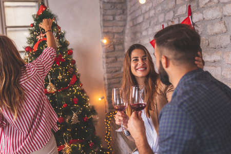 Beautiful young couple in love making a toast raising glasses of wine while decorating Christmas tree with friends, getting ready for New Year's Eve party at home Stockfoto