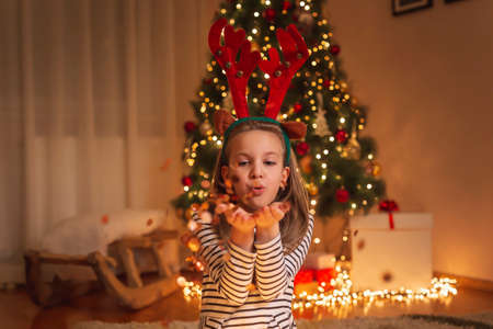 Beautiful little girl wearing costume reindeer antlers, sitting near nicely decorated Christmas tree, holding sparklers and having fun while celebrating New Year's Eve at home