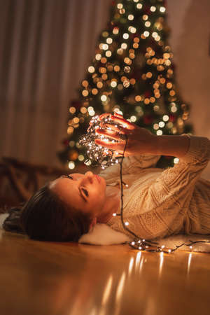 Beautiful young woman lying on the floor by nicely decorated Christmas tree, relaxing at home and enjoying winter holoday season