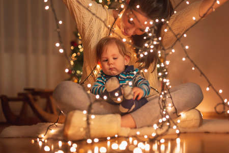 Mother and baby boy having fun spending New Year's Eve at home, lying on the floor next to a nicely decorated Christmas tree, playing with Christmas lights