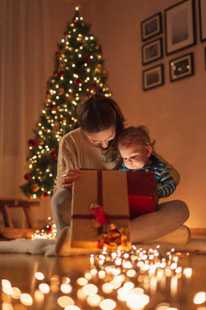 Beautiful mother holding her little son in her lap, sitting by nicely decorated Christmas tree and having fun opening magical glowing Christmas present