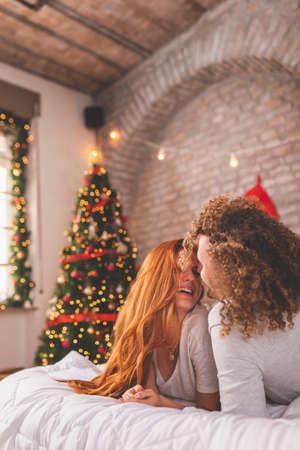 Couple in love wearing pajamas and costume reindeer antlers having fun taking selfies in bed on Christmas morning