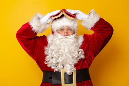 Santa Claus holding a lantern with candle and waving towards the camera isolated on yellow colored background 版權商用圖片