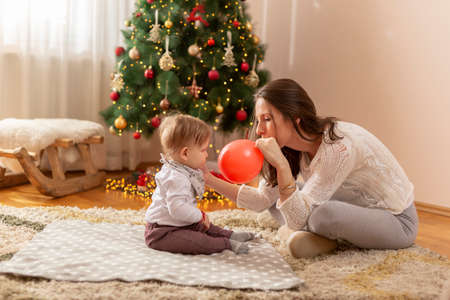 Beautiful young mother and baby boy having fun at home on Christmas day, sitting by nicely decorated Christmas tree, child playing inside of the giant Christmas gift box