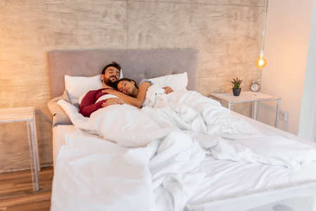Beautiful young couple in love lying in bed after waking up in the morning, laughing, hugging and enjoying time together Imagens