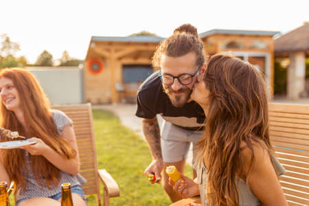 Beautiful young couple in love having fun with friends at backyard barbecue party, kissing and enjoying sunny summer days outdoor