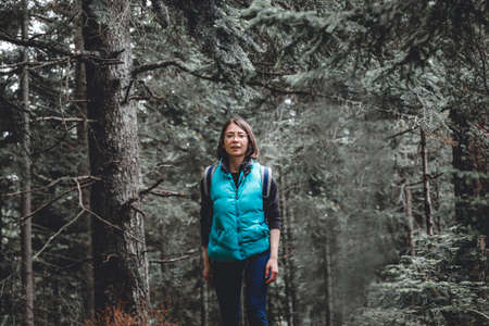 Young woman hiking through a beautiful evergreen forest in the mountains, spending an active day outdoors, relaxing in nature