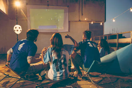 Group of young friends watching a football match on a building rooftop terrace, drinking beer and cheering for their team