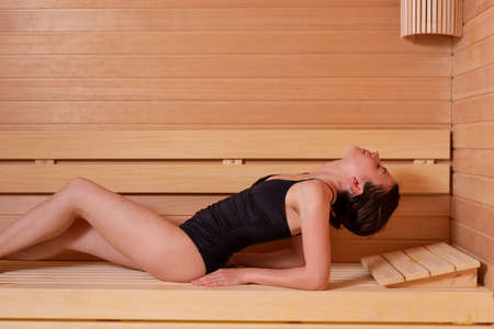 Beautiful young woman lying at sauna bench, relaxing and enjoying finnish sauna session and beauty treatments in spa center