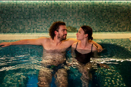 Beautiful young couple in love relaxing and enjoying finnish sauna session at spa center
