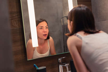 Beautiful young woman standing in front of mirror next to a sink in bathroom, brushing her teeth while getting ready for bed