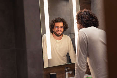 Handsome young man wearing pajamas standing in front of mirror in bathroom, getting ready for bed, brushing teeth and washing his face Banque d'images
