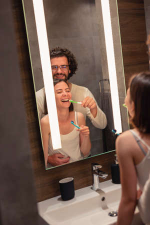Beautiful young couple in love wearing pajamas, standing in front of bathroom mirror next to a sink, having fun brushing teeth before bedtime together Banque d'images