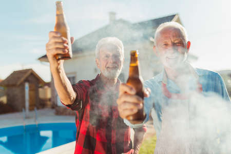 Two senior men making a toast with bottles of beer while grilling meat at backyard barbecue party by the swimming pool, relaxing outdoors on sunny summmer day Banque d'images