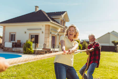 Senior couple having fun playing tug of war game, spending sunny summer day outdoors; group of elderly friends participating in rope pulling competition at retirement home