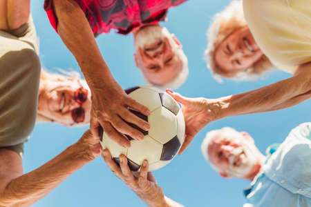 Senior people having fun playing tug of war game, spending sunny summer day outdoors; group of elderly friends having fun participating in rope pulling competition Banque d'images