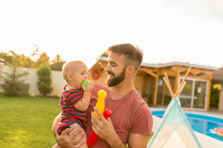 Young father holding his baby boy in his arms, carrying him around while playing in the backyard by the swimming pool on a sunny summer day, boy biting a ball Banque d'images