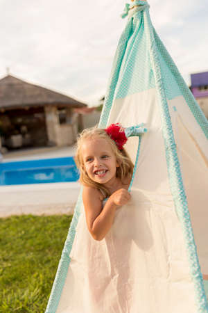 Beautiful cheerful little girl having fun while looking out through a tent window while camping in the backyard by the swimming pool Banque d'images