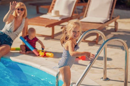 Beautiful young mother having fun playing with her kids by the swimming pool, enjoying hot sunny summer day outdoors