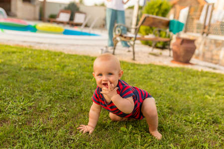 Beautiful baby boy playing with his parents in the backyard, crawling on the lawn Banque d'images