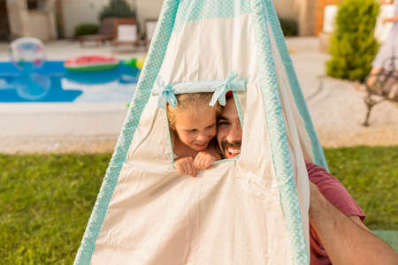 Father playing hide and seek with his little daughter while camping in the backyard by the swimming pool, having fun peeking out of the tent window while hiding Banque d'images