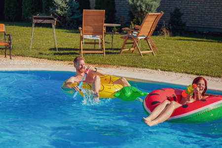 Beautiful young couple in love having fun swimming and splashing water on each other in the pool, climbing and jumping of a pool float, relaxing while on a summer vacation