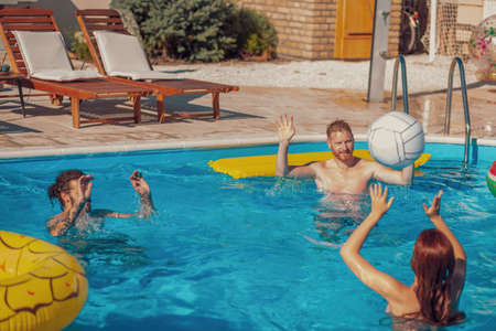 Group of friends having fun outdoors on a hot sunny summer day, playing volleyball in the swimming pool, relaxing while on a summer vacation