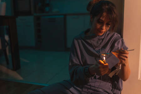 Junike shooting up with heroin; female drug addict injecting herself with heroin dose intravenously; drug addiction and substance abuse concept. Focus on the tourniquet