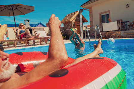 Group of elderly people having fun spending hot summer day at the swimming pool, sunbathing, floating on air mattress and splashing water on each other, cooling down and relaxing