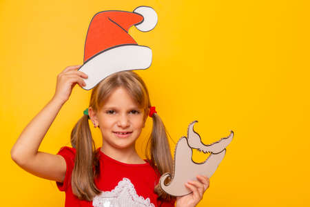 Beautiful little girl wearing Santa hat peeking from large Christmas present isolated on yellow colored background