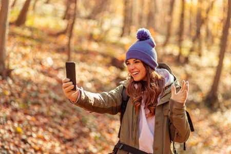 Active young woman holding a compass and reading a map while taking a hiking break, having fun and relaxing while spending autumn day outdoors Foto de archivo