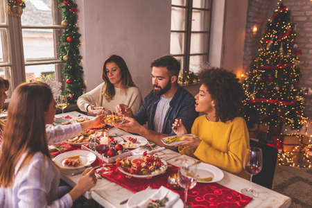 High angle view of group of friends making a toast during Christmas dinner, raising glasses of wine and celebrating Christmas day together at home Foto de archivo