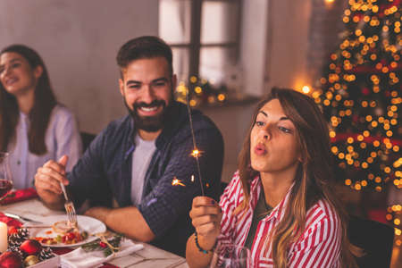 Lonely woman spending Christmas Eve with friends at home, sad while sitting over Christmas dinner surrounded with couples in love Foto de archivo