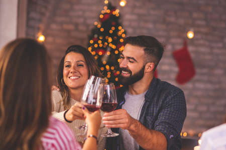 Group of friends making a toast during Christmas dinner, raising glasses of wine and celebrating Christmas day together at home