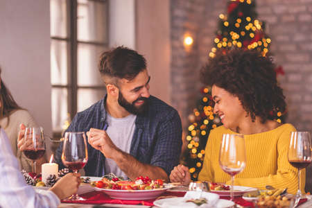 Group of cheerful young friends having fun celebrating Christmas, gathered around the table, eating dinner, drinking wine and having fun while spending time together