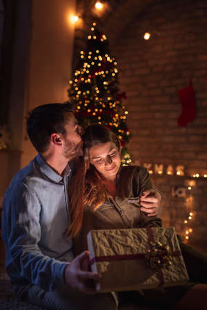 Young couple in love sitting next to a nicely decorated Christmas tree, opening presents and having fun while spending Christmas Eve together at home Foto de archivo