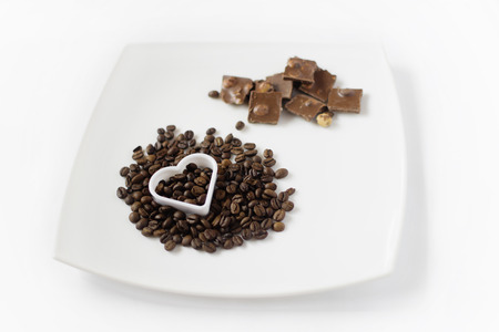 Plate with coffee and chocolate and baking tins in the form of heart photo