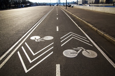 Bicycle white sign or icon on the asphalt road in the city Stock fotó