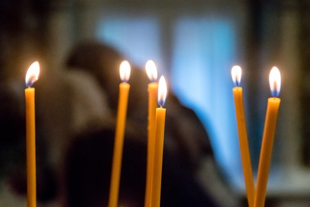 long lighted candles group in a church. selective focus