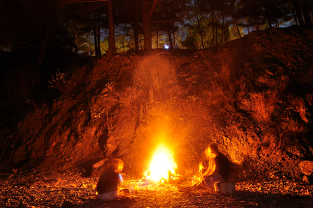 Hiking tourists have a rest around camp fire in mountains night