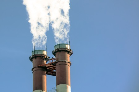 smoke coming out of pipes into the clear blue sky, ecology problems Stock Photo