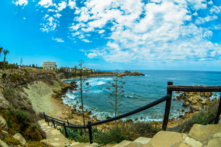 sea surface and sunny summer rocky coastline with clouds