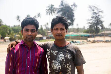 India, Goa, March 31 2017: Couple of asian male friends on Arambol beach