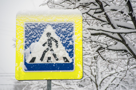 Pedestrian crossing traffic sign after snow storm