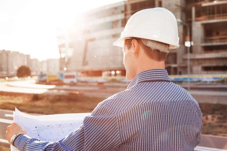 Chief Engineer met blauwdruk in de hand te kijken naar de bouwplaats. Uitzicht vanaf de achterkant