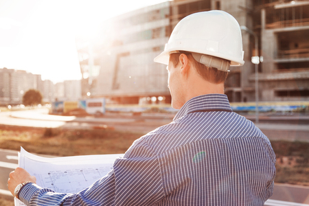 Chief Engineer with blueprint in hand looking at the construction site. View from the back