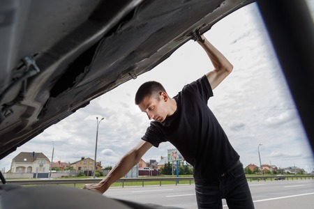 motor cars: Closeup portrait, young man having trouble with his broken auto, opening hood trying to fix engine, isolated green trees outside background. Stock Photo