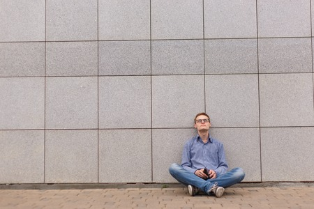 building wall: hopeless businessman sitting on the office building wall background Stock Photo